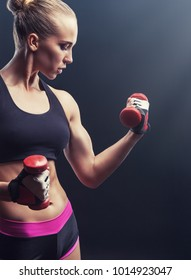 Beautiful athletic woman with red dumbbells against a dark background