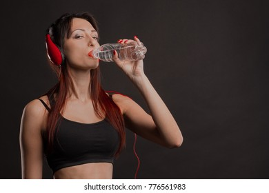 Beautiful athletic woman in red headphones drinking water