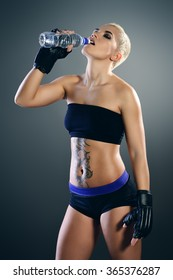 Beautiful athletic woman standing with a bottle of clear water after training. Sports, healthcare.