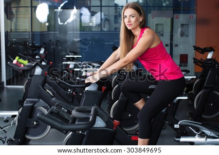 611c9b1124de5 Beautiful athletic woman, wearing in shirt and leggings, posing on exercise  bike in gym