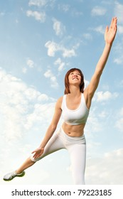 Beautiful athletic woman in white sportswear balancing in front of blue sky