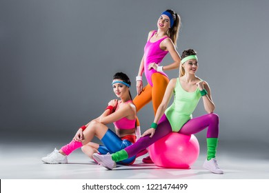 beautiful athletic women in 80s style sportswear posing together on grey