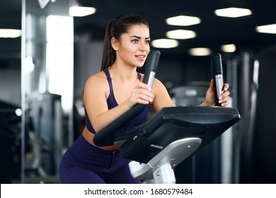 A beautiful athletic young brunette woman in sportswear in the gym is engaged on a bike. Healthy lifestyle.