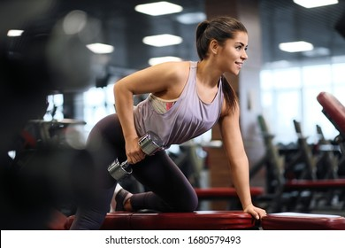 A beautiful athletic young brunette woman in sportswear in the fitness room raises dumbbells lying down and standing.