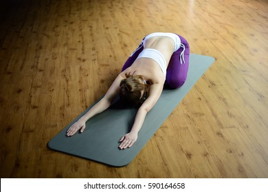 Beautiful athletic young female make yoga Balasana or Child's Pose