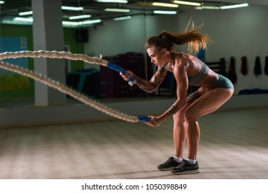 Beautiful, athletic, young girl in green shorts and t-shirt, does exercises with ropes in a large spacious sports hall. Dense and very relief.