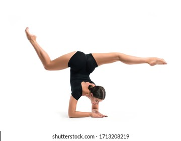 Beautiful athletic young girl gymnast in sportswear, training, element of gymnastics, performs exercises on a white background. Sports motivation, stretching, physical education