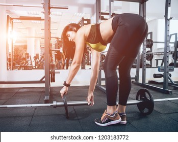 Beautiful athletic young woman making exercise at the gym. Young woman with muscular body. Fitness concept.
