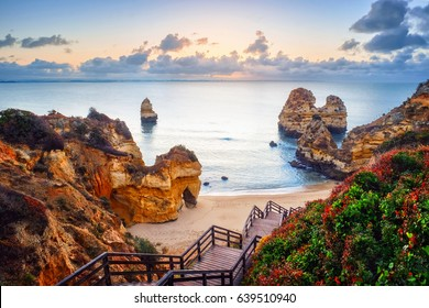beautiful Atlantic ocean view horizon with sandy beach,  rocks and waves at sunrise. Algarve,  Portugal