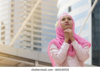 Beautiful Attractive Arab or Muslim woman praying for god in city