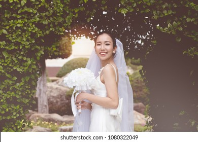 Beautiful Attractive Asian Bride Woman wearing white wedding dress and holding bouquet smile so proud and happiness in wedding day,Bride Concept
