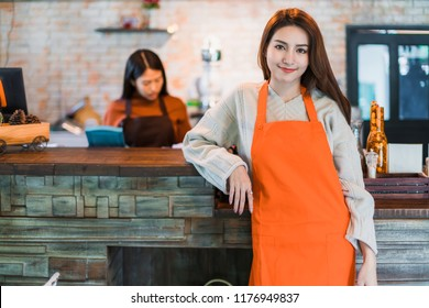 beautiful attractive asian cafe shop owner smile with happiness and joyful with coffee cup apron cafe  background