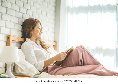 Beautiful Attractive Asian woman sitting on bed in bedroom reading book for learn and education smile and positive thinking feeling so happiness and comfortable,Education Concept