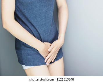 Beautiful Attractive Asian woman wearing white shirt sitting on bed have a bladder pain or uti pain after wake up in the morning feeling so illness,Healthcare Concept.
