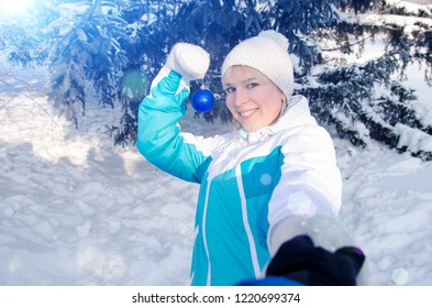 beautiful attractive blonde girl holds in her hands a ball to decorate a Christmas tree and pulls the viewer to decorate the Christmas tree