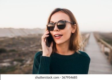Beautiful attractive blonde young woman talking on phone while walking on the beach path.