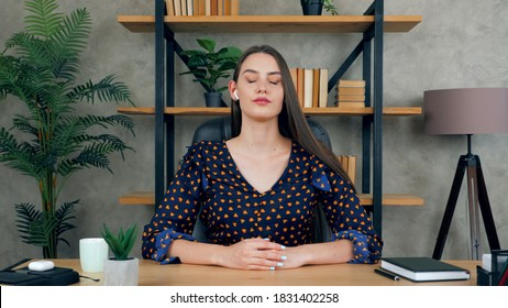 Beautiful attractive brunette woman wears wireless earphones meditates with closed eyes sitting on chair at desk in home office, resting after hard work listening to calm music audio sounds