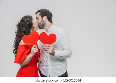 Beautiful attractive, cheerful, positive pair. Are married Hold big red cards in their hands. During this time they kiss.