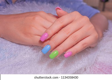 beautiful attractive colorful gel nail art on fashionista young woman fingernails isolated on white fur background
