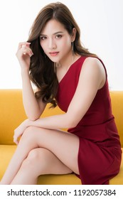 beautiful attractive elegance asian woman in red dress  sit and relax model pose on yellow sofa studio photo shoot