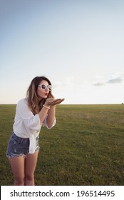 Beautiful, attractive and fashion woman on green field, blowing from her hands, wearing sexy denim shorts, white shirt and sunglasses