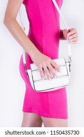 Beautiful attractive female in pink summer dress and white handbag in hand isolated on white background. Fashion and beauty concept. Close up, selective focus