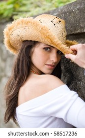 beautiful and attractive female in straw hat looks into camera, stone wall as background