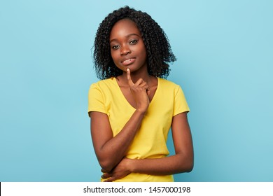 beautiful attractive girl holding index finger on chin, having doubt and suspicion feeling, close up portrait.isolated blue background.beauty concept