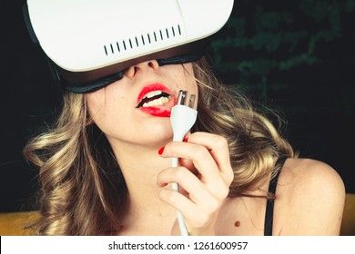 Beautiful attractive girl holds a cable in her hand and widely opened mouth with tongue sticking out. Illustration of virtual oral sex. Concept of increasing potency through the Internet and blowjob