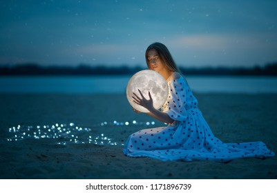 Beautiful attractive girl on a night beach with sand and stars hugs the moon, Artistic Photography