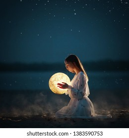 Beautiful attractive girl on a night beach with sand and stars hugs the moon,