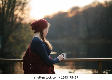 Beautiful attractive girl in a red hat on the lake in autumn holds a mug in her hands. Without face