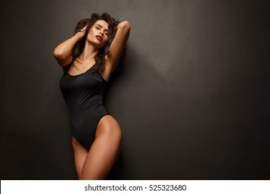 Beautiful and attractive girl with sexy shapely forms, loose wavy hair, red open lips and slim figure is posing in the black body, studio photoshoot, dark background