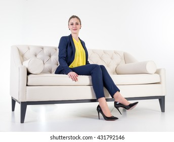 Beautiful attractive girl sitting on modern sofa in white room