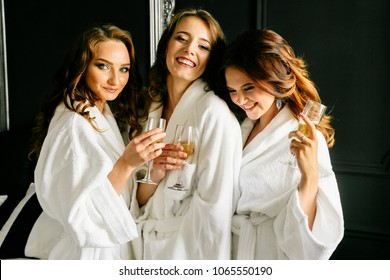 Beautiful attractive girls laugh and drink champagne in white coats on black wall background