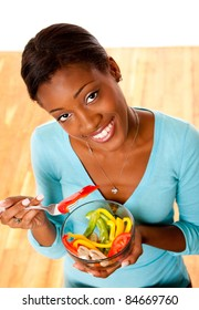 Beautiful attractive happy smiling health conscious young woman eating healthy salad from a bowl.