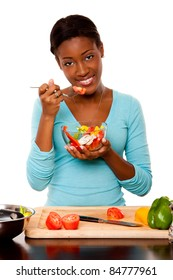 Beautiful attractive happy smiling health conscious vegetarian  young woman eating healthy fresh organic salad from a bowl, standing at kitchen counter with chopping board, isolated.