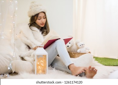 Beautiful attractive mole woman with white fur hat and sweater read book in bedroom at winter with copy space for text. Smile girl relax in house during Christmas holiday.