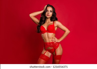 Beautiful, attractive, pretty, dreamy, charming, elegant lady in boudoir lace on suspenders with wavy hairstyle hold hand on head and waist look at camera isolated on vivid red background