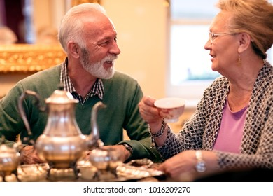 Beautiful attractive senior couple smiling and drinking tea at nursing home