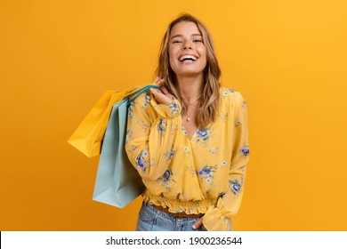 beautiful attractive smiling woman in yellow shirt and jeans holding shopping bags posing on yellow background isolated