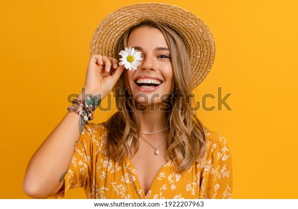 beautiful attractive stylish woman in yellow dress and straw hat holding daisy flower romantic mood posing on yellow background isolated in love summer fashion trend style, natural look