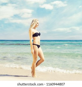 Beautiful and attractive woman in black bikini. Young girl posing on a beach. Traveling, vacation, holiday, tourism, concept.