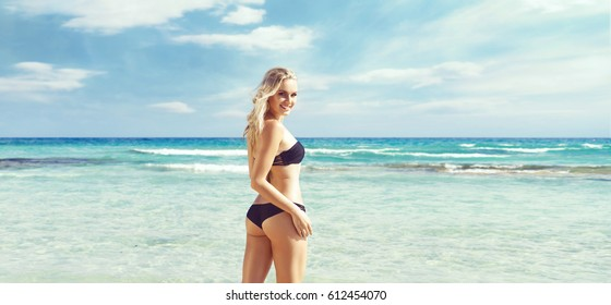 Beautiful and attractive woman in black bikini. Young girl posing on a beach at summer. Traveling, vacation, holiday, tourism, concept.