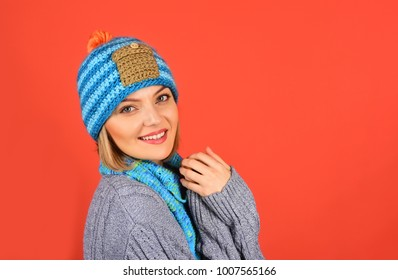 Beautiful attractive woman dressed in warm sweater, hat and scarf. Glamorous fashion portrait of beautiful charming girl in winter clothes. Winter concept. Copy space to advertise the clothing store.