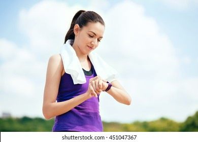 Beautiful attractive woman making outdoor before or after workout and running in park, checking her running time. In purple t-shirt and white towel on nature background. Look at the watch.Sport