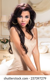 Beautiful and attractive young adult female brunette sensuality woman posing on bed in exclusive apartment