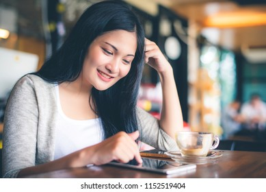 Beautiful attractive young Asian woman using smart phone or cellphone at cafe or coffe shop in the morning