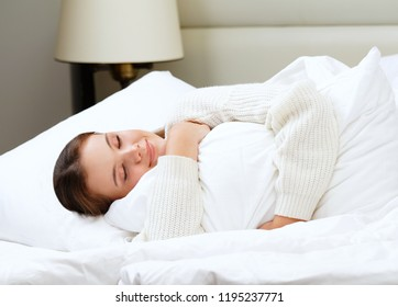 beautiful attractive young caucasian woman brunette morning lying in white bed holding pillow slipping