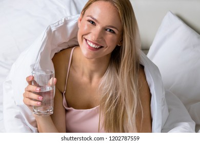 beautiful attractive young caucasian woman with computer laptop blond morning in white bed with glass of water in hand looking at camera face smiling